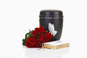 Feuerbestattung - Urne mit Blumen und Gebetsbuch